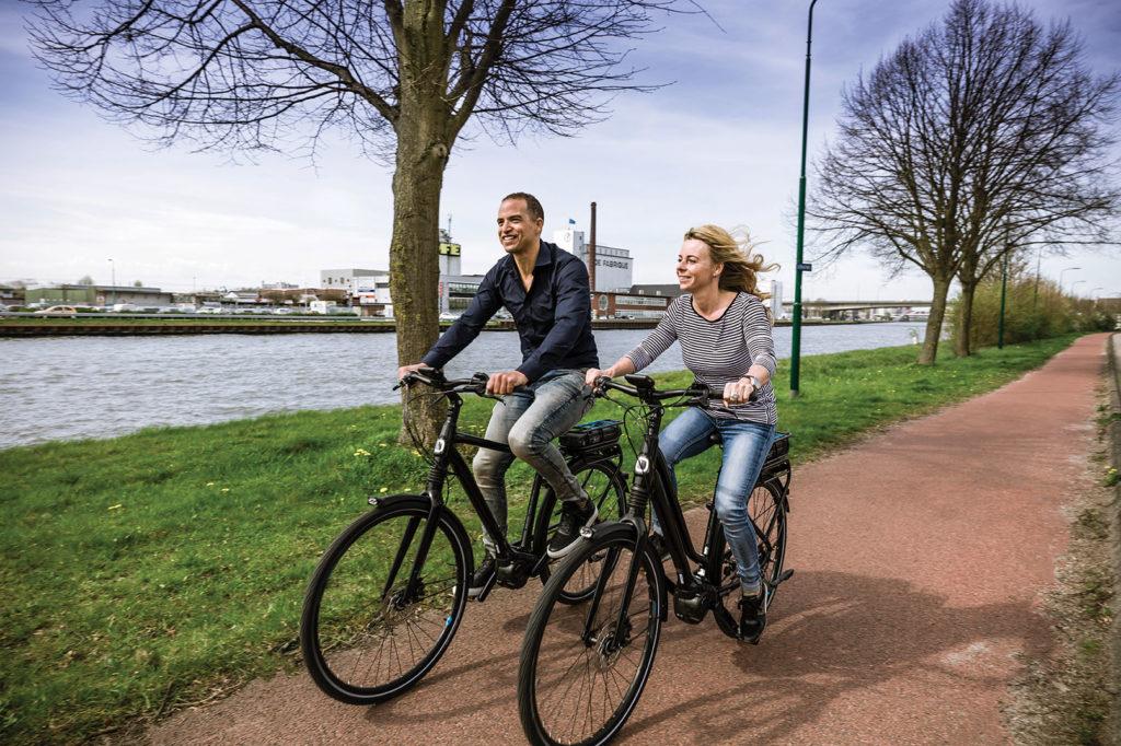 man en vrouw fietsen langs een vaart op een Giant fiets