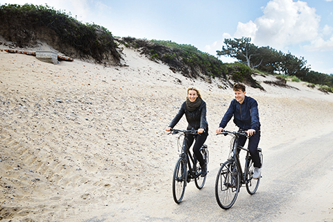 een man en een vrouw fietsen op toerfietsen