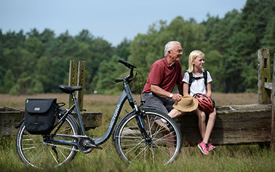man en kind in het bos bij een Victoria fiets
