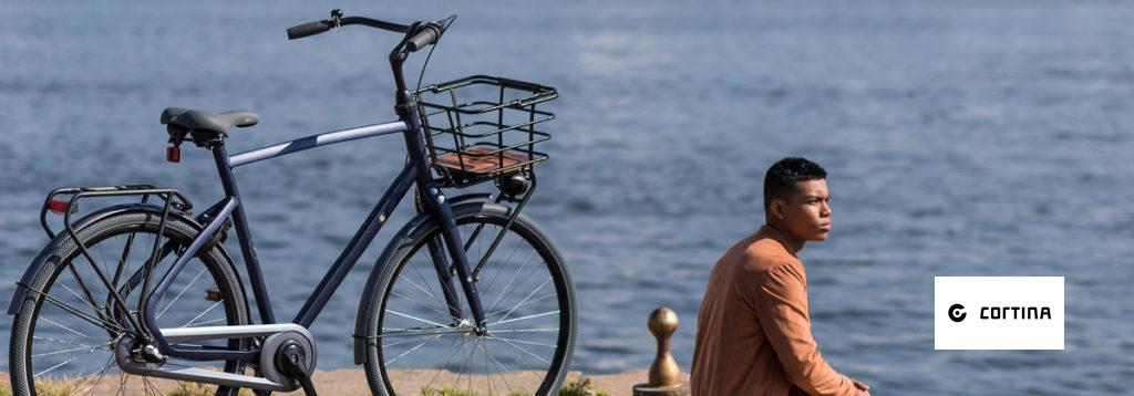 man zit naast een cortina fiets aan de waterkant