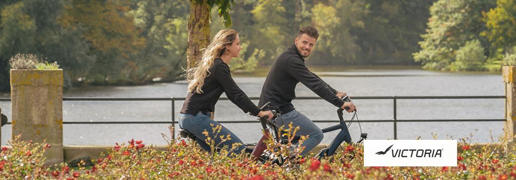 man en vrouw fietsen op een Victoria elektrische fiets langs het water door een park